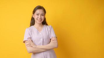 asiatische Frau, die mit verschränkten Armen lächelt und Kamera auf gelbem Hintergrund betrachtet foto