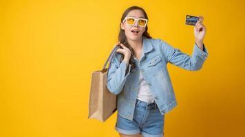asiatische Frau lächelnd und hält eine Kreditkarte und eine Papiereinkaufstasche auf gelbem Hintergrund foto