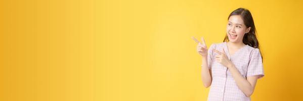 asiatische Frau, die lächelt und zum Kopierraum auf gelbem Hintergrund gestikuliert foto