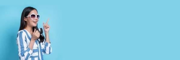 asiatische Frau mit weißer Sonnenbrille, die zum Kopierraum auf blauem Hintergrund gestikuliert foto