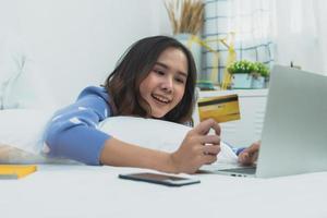 asiatische Frau, die Kreditkarte hält, die auf Laptop liegt, der auf Bett im Schlafzimmer liegt