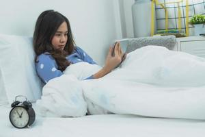 asiatische Frau, die Tablette betrachtet, die auf Bett im Schlafzimmer liegt