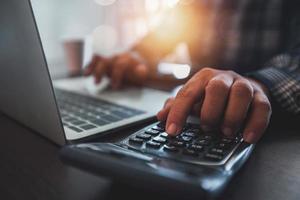 Nahaufnahme der Hand des Geschäftsmannes unter Verwendung des Taschenrechners und der Arbeit am Laptop foto