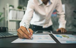 Nahaufnahme des Geschäftsmannes, der auf Papieren von Diagrammen und Grafiken neben Tablette und Laptop schreibt