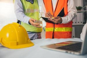 Bauarbeiter schreiben in Notizbuch neben Laptop und Schutzhelmen