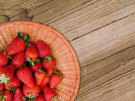 Erdbeeren in einer Weidenschale auf einem Holztischhintergrund foto