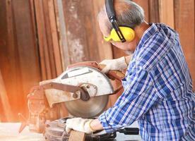 Der ältere asiatische Zimmermann verwendet eine Kreissäge, um Holz für Möbel zu verarbeiten foto