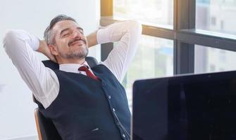 glücklicher junger Geschäftsmann, der an einem modernen Büro ruht foto
