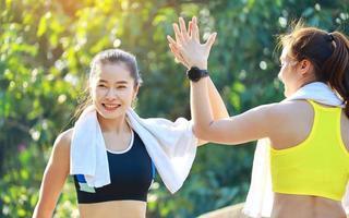 zwei schöne Frauen, die draußen im Park trainieren foto