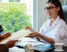 junge Unternehmerin, die in einem modernen Büro sitzt und einen braunen Umschlag erhält foto