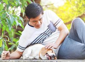 asiatischer Mann mit seinem Hund im Urlaub im Park foto