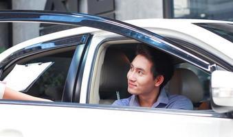 Der hübsche junge asiatische Mann hat kürzlich ein neues Auto in einem Ausstellungsraum gekauft foto