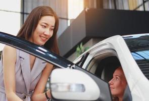 Frau kauft ein neues Auto aus einem Ausstellungsraum foto