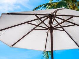weißer Regenschirm mit Kokospalme foto