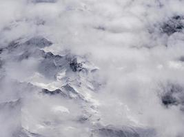 Luftaufnahme von Bergen, die mit Wolken oder Nebel bedeckt sind foto