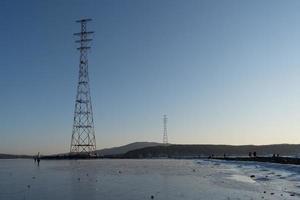Seelandschaft von Wasser und Bergen mit Stromübertragungstürmen in Wladiwostok, Russland foto