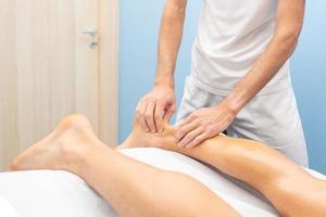 Physiotherapeut während einer Achillessehnenbehandlung foto