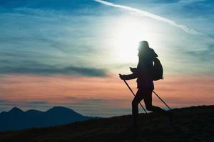 Silhouette eines Mädchens auf einem Berg während einer religiösen Wanderung in einem blauen und orangefarbenen Himmel. foto