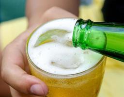 Person, die ein Bier einschenkt foto