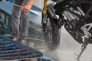 Person, die ein Motorrad wäscht foto