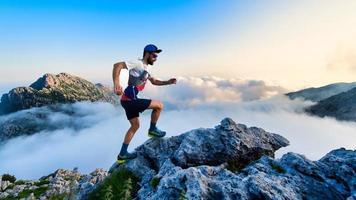 männlicher Ultramarathonläufer in den Bergen während eines Trainings foto