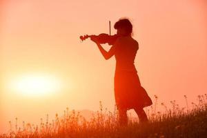 Frau, die eine Geige in einem roten Sonnenuntergang in der Natur spielt foto