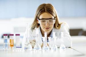 Ärztin oder wissenschaftliche Forscherin, die einen Kolben mit Lösungen in einem Labor betrachtet foto