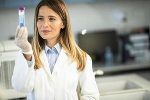 Ärztin mit schützender Gesichtsmaske im Labor, die den Kolben mit flüssiger Probe hält foto