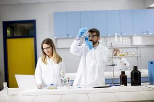 Forscher arbeitet mit blauer Flüssigkeit am Laborglas foto