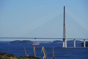 Seelandschaft der russischen Brücke und einer Küste mit Baukränen in Wladiwostok, Russland