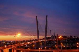 goldene Brücke mit buntem Sonnenuntergangsonnenuntergang in Wladiwostok, Russland foto
