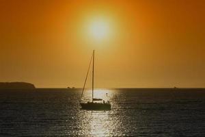 Silhouette einer Yacht im Wasser mit einem leuchtend orangefarbenen Sonnenuntergang in Wladiwostok, Russland foto