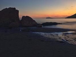 Mittelmeerstrand ohne Menschen bei Sonnenuntergang in Calpe, Alicante
