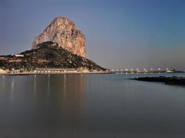 Mittelmeerstrand bei Sonnenuntergang mit dem Penon im Hintergrund in Calpe, Alicante foto