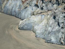 Felsen mit geraden Kanten bei Ebbe eines Strandes an der asturischen Küste foto