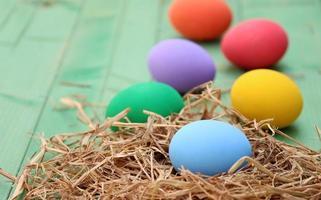 Ostereier in einem Nest auf einem hölzernen Hintergrund