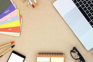Draufsicht auf einen hölzernen Schreibtisch-Tisch mit einem Laptop, einem Smartphone, einem Buch und Zubehör