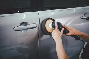 Mann poliert ein graues Auto foto