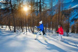 Paar Freundinnen gehen mit Schneeschuhen bei Sonnenuntergang, Foto auf Lager