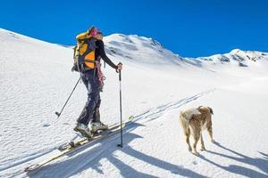 Mädchen macht Skibergsteigen mit Hund foto