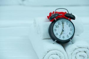 Weckkonzept des schwarzen Weckers auf dem Bett foto