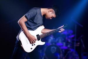 junger Mann mit E-Gitarre im Studio foto