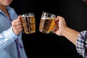 beschnittenes Bild von gutaussehenden Freunden, die zu Hause Bierflaschen anstoßen