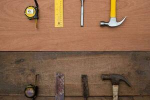 Draufsicht auf einen alten Hammer, Meißel, Maßband gegen einen Satz neuer Handwerkzeuge auf einer hölzernen Werkbank foto