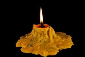eine brennende Kerze, die hell auf einem schwarzen Hintergrund brennt foto