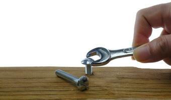 eine Hand mit einem Schraubenschlüssel, der eine Schraube in ein Holzbrett auf einem weißen Hintergrund schraubt foto