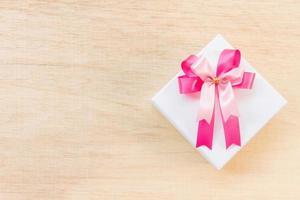 rosa Bandschleife auf einer weißen Geschenkbox auf einem hölzernen Hintergrund foto