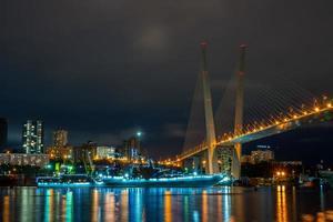 Stadtlandschaft der goldenen Hornbucht, eines Schlachtschiffs und der goldenen Brücke in Wladiwostok, Russland foto