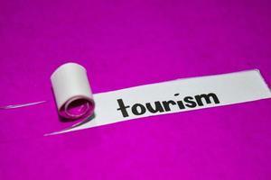 Tourismus Text, Inspiration, Motivation und Geschäftskonzept auf lila zerrissenem Papier foto