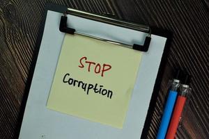Stoppen Sie Korruption geschrieben auf Haftnotiz isoliert auf Holztisch